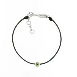 Bracelet sur cordon noir et sa pierre vert Péridot dans son serti clos argent par Elsa Lee.